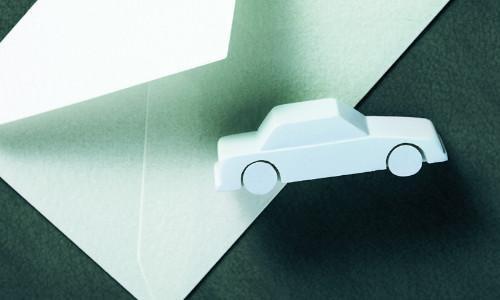 Ein graues Spielzeugauto liegt auf einem weißem Briefumschlag