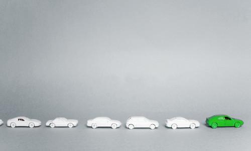 Sechs Spielzeugautos fahren in einer Reihe. Das vorderste Auto ist grün, die anderen grau.
