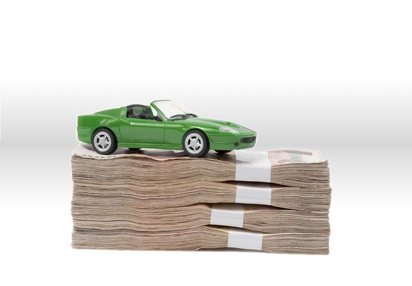 Ein grünes Spielzeug auf einem Stapel Geldscheinen.