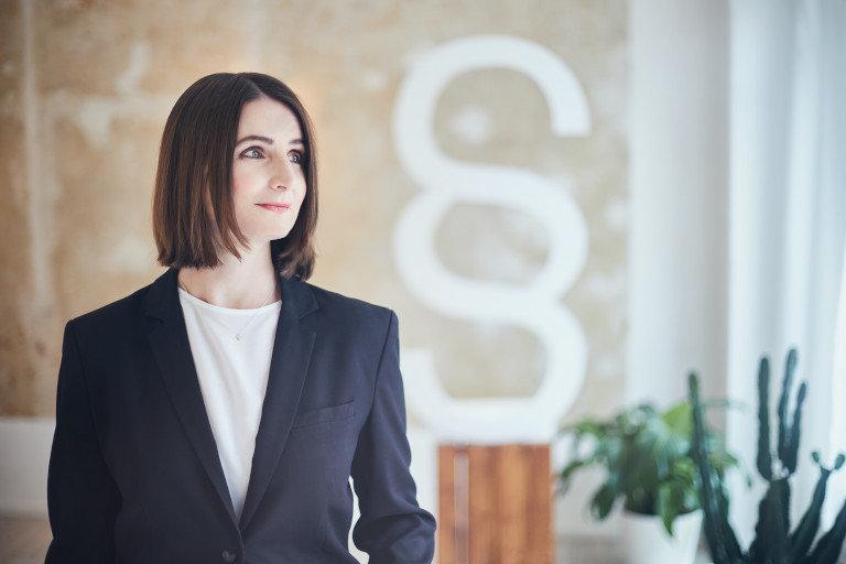 Eien Portrait Fotografie von der Rechtsanwältin Jacqueline Kröhnert einem Büro.