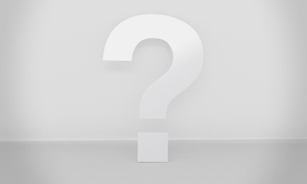 Weißes dreidimensionales Fragezeichen ine einem grauen Raum