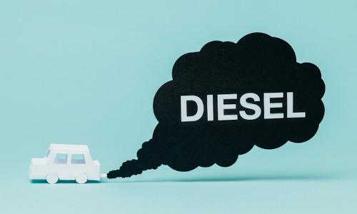 weißes Auto auf blauem Hintergrund mit schwarzer Abgaswolke in dem Diesel steht