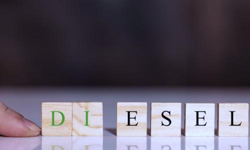 Ein Finger schiebt das Wort Diesel mit Bauklötzen zusammen