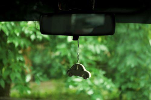 Ein grüner Duftspender hängt im Auto