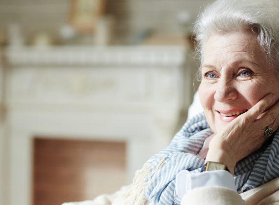 eine lächelnde ältere dame am Kamin