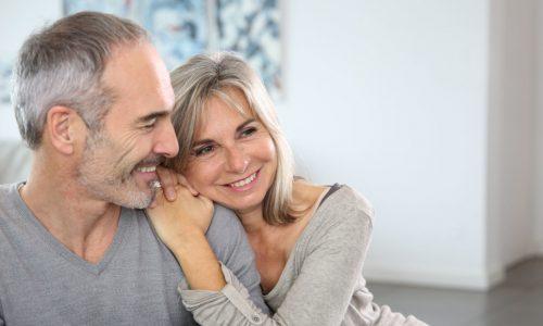 Älteres Ehepaar sitzt lachend auf dem Sofa und umarmt sich