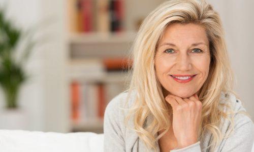 Eine Blonde ältere Dame auf einem Sofa. Im Hintergrund ein Bücherregal