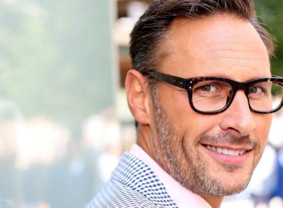 Mann mittleren Alters mit Brille und Anzug lehnt sich an eine Wand an.