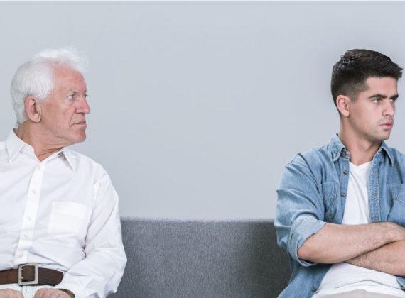 Ein älterer und ein jüngerer Herr sitzen gemeinsam auf der Couch und sind verägert