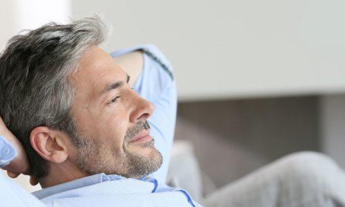 attracktiver Mann sitzt mit Händen hinter dem Kopf auf der Couch