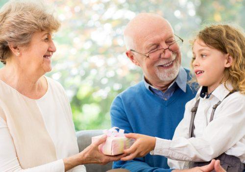 Großeltern sitzen mit ihrer Eknelin auf einer Couch und Schenken ihr ein kleines Päckchen.